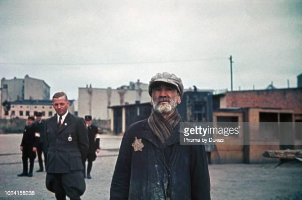 Ghetto Lodz Litzmannstadt Hans Biebow chief ofÊGerman Nazi administration of the ghetto and Jewish policemen watch an old jew Poland 1940 World War II