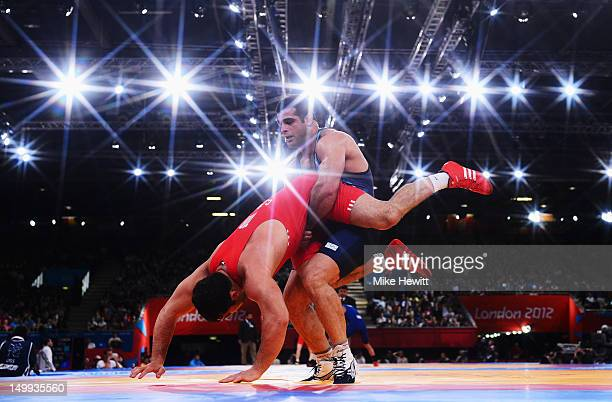 Gholamreza Ghasem Rezaei of Iran throws Cenk Ildem of Turkey during their Men's Greco-Roman 96kg 1/8 Final on Day 11 of the London 2012 Olympic Games...