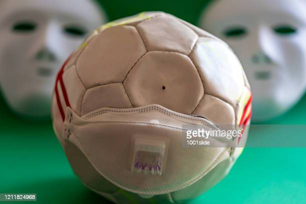 ghost audience, deflated ball with mask on the green - football world is very poor against the corona virus - football face mask stock pictures, royalty-free photos & images