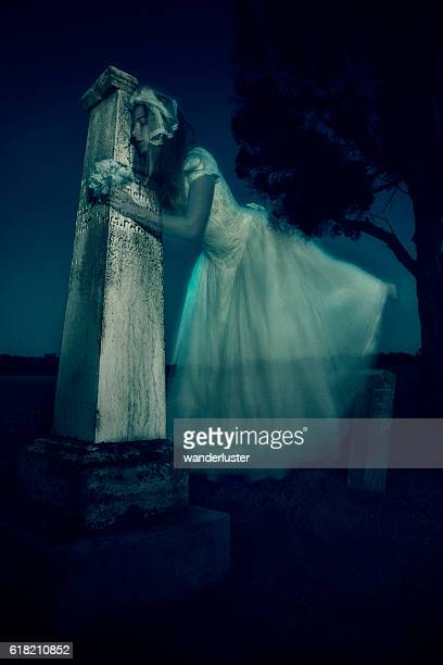 Ghost bride in vintage wedding dress hugs headstone