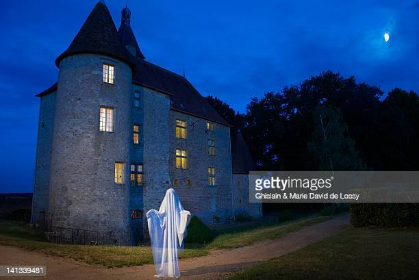 Ghost floating outside stone house