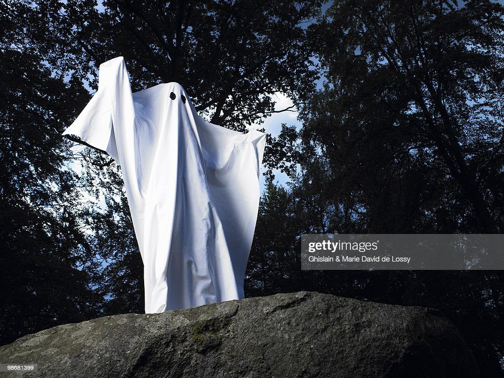 Ghost made of sheets, standing on a rock : Stock Photo