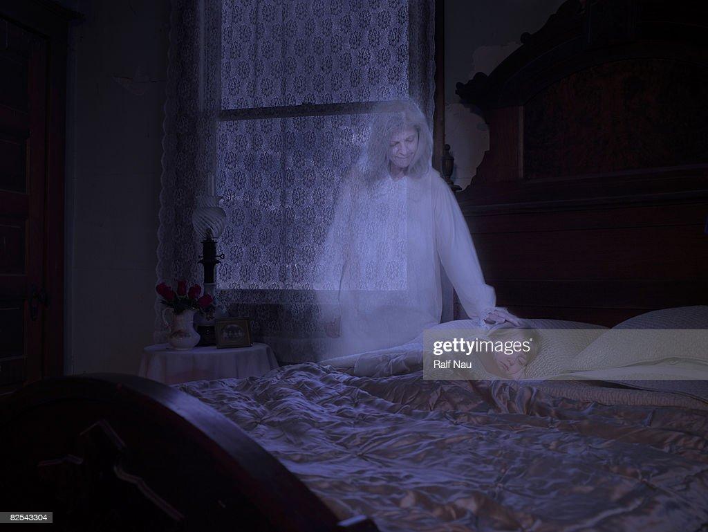 Ghost touching sleeping granddaughter : Stock Photo