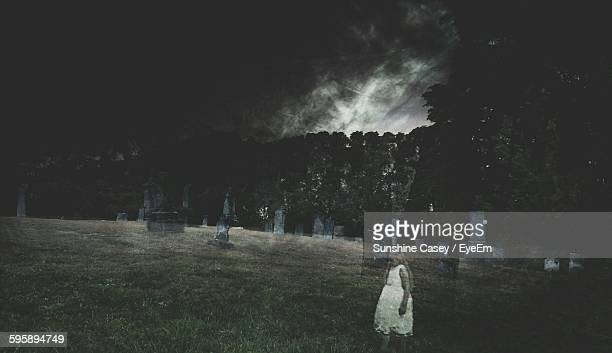 ghost walking at cemetery against sky at night - cemetery stock photos and pictures