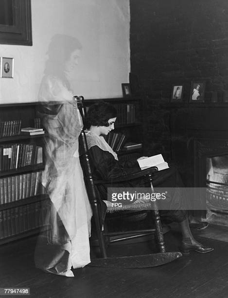 A ghostly apparition appears behind a young woman who sits reading oblivious to her spectral companion circa 1925