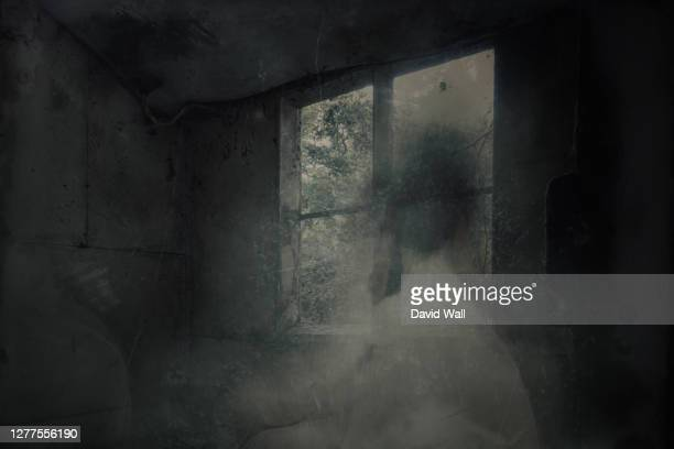 a ghostly, blurred woman in a dress. looking out of a window in a spooky abandoned house. with a grunge, vintage, old textured edit - dirty stock pictures, royalty-free photos & images