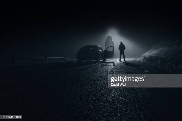 a ghostly blurred woman in a dress standing floating on a country road at night. with a car and driver behind. - dress stock pictures, royalty-free photos & images