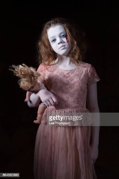 ghostly girl holding a doll - zombie girl stock photos and pictures