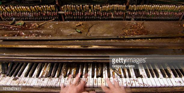 ghostly hands playing an old weathered and broken piano - grimes musician stock pictures, royalty-free photos & images