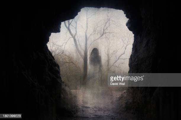 a ghostly transparent woman. standing in the entrance of a cave. on an atmospheric winters day. with a grunge, blurred vintage edit. - women wearing see through clothing stock pictures, royalty-free photos & images
