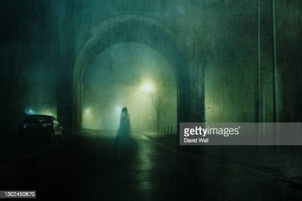 a ghostly transparent woman. standing underneath an arch of a bridge. on an atmospheric winters night in town. with a grunge, blurred vintage edit. - women wearing see through clothing stock pictures, royalty-free photos & images
