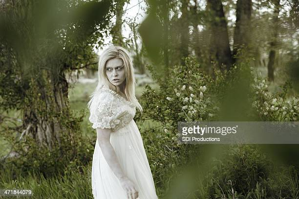 Ghostly woman walking through heavily wooded area