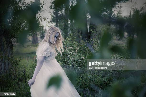 Ghostly woman wearing white dress in wooded area