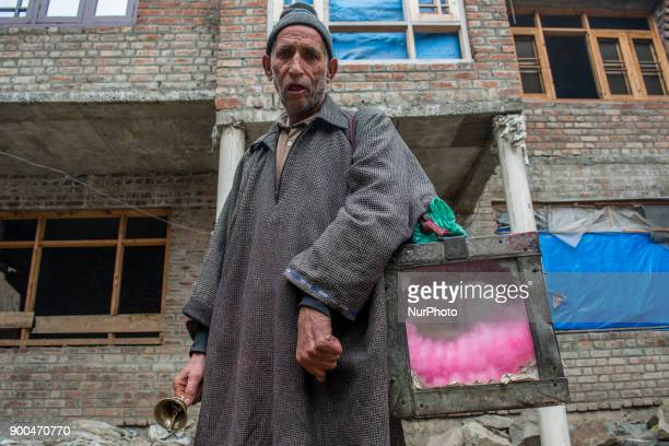 Ghulam Muhammad Bhat poses with his glass box full of cotton candies or candy floss before selling them to children outside his home on January 2 in...