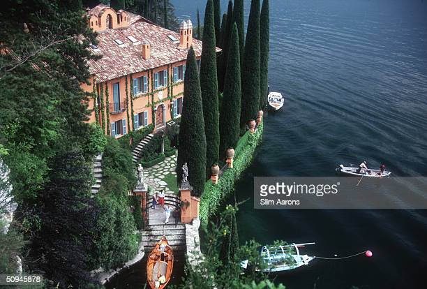 Giacomo and Stefania Montegazza welcome guests arriving by boat at their villa La Cassinella on Lake Como 1983