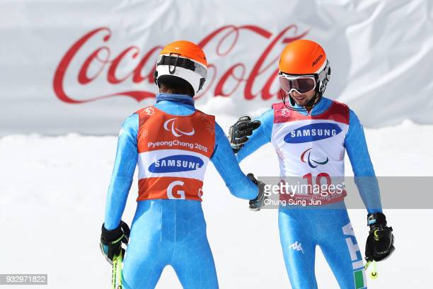 Giacomo Bertangnolli of Italy celebrates with his guide Fabrizio Casal after winning the Alpine Skiing Men's Slalom Visually Impaired during day...