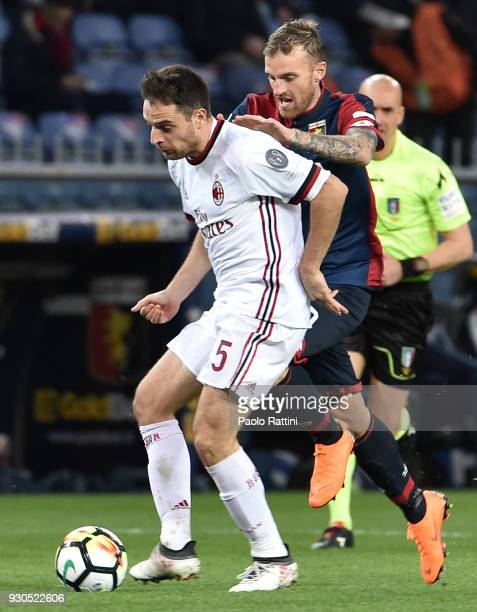 Giacomo Bonaventura of Milan is tackled by to Luca Rigoni of Genoa during the serie A match between Genoa CFC and AC Milan at Stadio Luigi Ferraris...