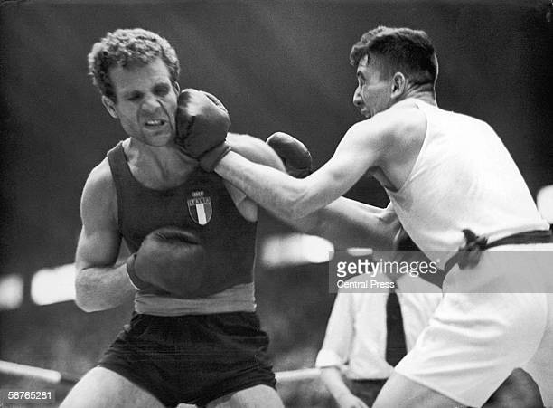 Giacomo de Segni of Britain takes a lefthanded punch from Donald Scott of Britain in the Olympic LightHeavyweight Boxing quarterfinals at Wembley...