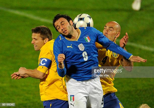 Giampaolo Pazzini of Italy competes for a header against Anders Svensson and Daniel Majstorovic of Sweden during the international friendly match...