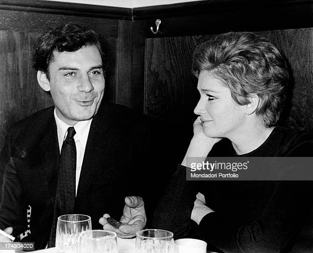 Gian Maria Volontè and Carla Gravina seated together at a dinner the two actors are lovers and they have a daughter named Giovanna Milan March 1968