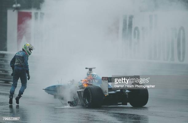 Giancarlo Fisichella of Italy, driver of the Mild Seven Benetton Playlife Benetton B198 Playlife GC37-01 V10 surveys the damage and flames coming...
