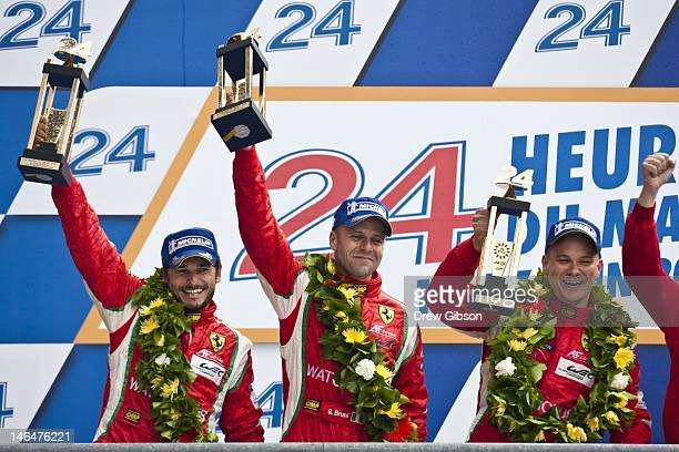 Giancarlo Fisichella of Italy Gianmaria Bruni of Italy and Toni Vilander of Finland celebrate on the podium after claiming GT class victory in their...