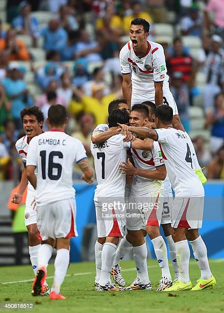 Giancarlo Gonzalez of Costa Rica jumps on his teammates as they celebrate the team's second goal by Oscar Duarte during the 2014 FIFA World Cup...