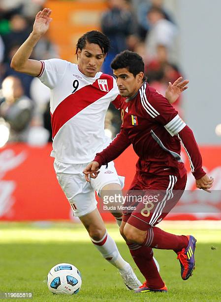 Giancarlo Maldonado of Venezuela struggles for the ball with Jose Paolo Guerrero of Peru during the Copa America 2011 third place match between...