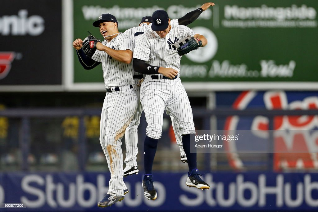 Giancarlo Stanton #27 and Aaron Judge #99 of the New York Yankees celebrate after defeating the Houston Astros at Yankee Stadium on May 30, 2018 in the Bronx borough of New York City. The Yankees won 5-3.