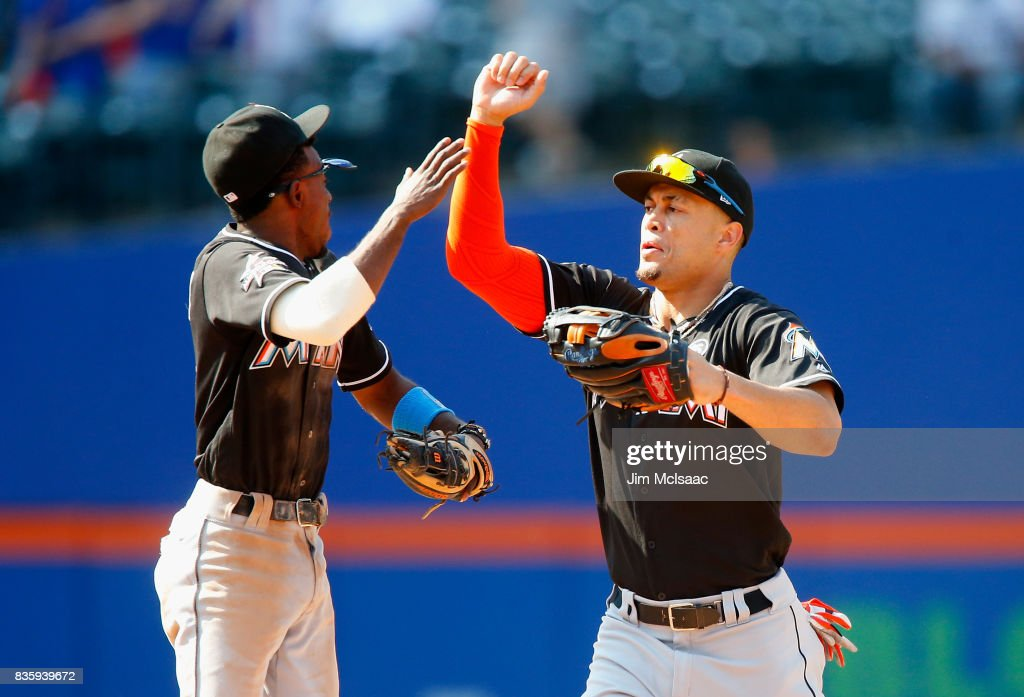 Giancarlo Stanton #27 and Dee Gordon #9 of the Miami Marlins celebrate after defeating the New York Mets at Citi Field on August 20, 2017 in the Flushing neighborhood of the Queens borough of New York City.