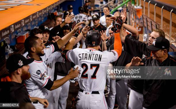 Giancarlo Stanton of the Miami Marlins celebrates in the dugout after hitting his fiftyninth home run of the season during the eighth inning of the...