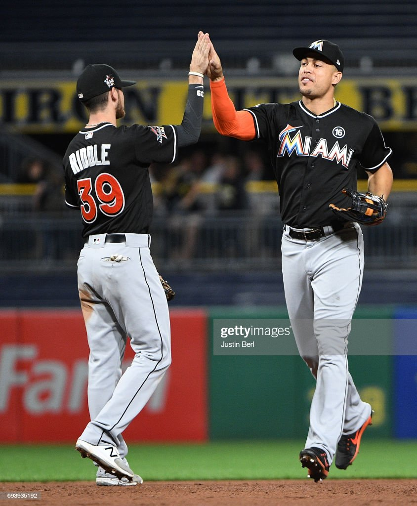 Giancarlo Stanton #27 of the Miami Marlins celebrates with JT Riddle #39 after the final out in the Miami Marlins 7-1 win over the Pittsburgh Pirates at PNC Park on June 8, 2017 in Pittsburgh, Pennsylvania.