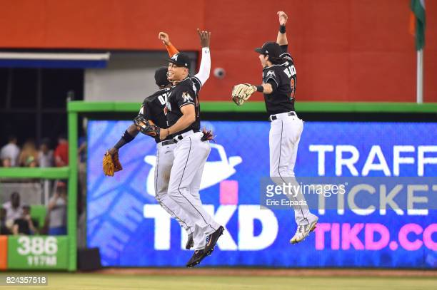 Giancarlo Stanton of the Miami Marlins celebrates with Marcell Ozuna and Christian Yelich after they defeated the Cincinnati Reds at Marlins Park on...