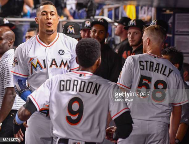 Giancarlo Stanton of the Miami Marlins celebrates with teammates in the dugout after hitting a homerun in the third inning during the game between...