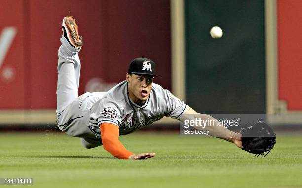 Giancarlo Stanton of the Miami Marlins dives but comes up short a soft fly ball by Carlos Lee of the Houston Astros that went for a triple in the...