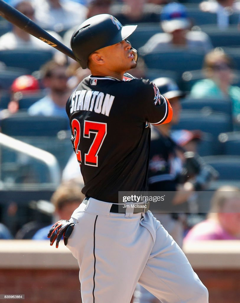 Giancarlo Stanton #27 of the Miami Marlins follows through on a seventh inning three run home run against the New York Mets at Citi Field on August 20, 2017 in the Flushing neighborhood of the Queens borough of New York City.