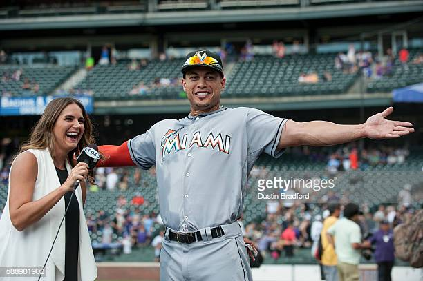 Giancarlo Stanton of the Miami Marlins gestures after being splashed by teammates after a 107 win over the Colorado Rockies as on field reporter...