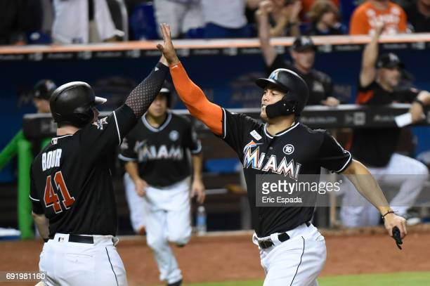 Giancarlo Stanton of the Miami Marlins high fives Justin Bour scoring on an RBI single by Marcell Ozuna against the Arizona Diamondbacks at Marlins...