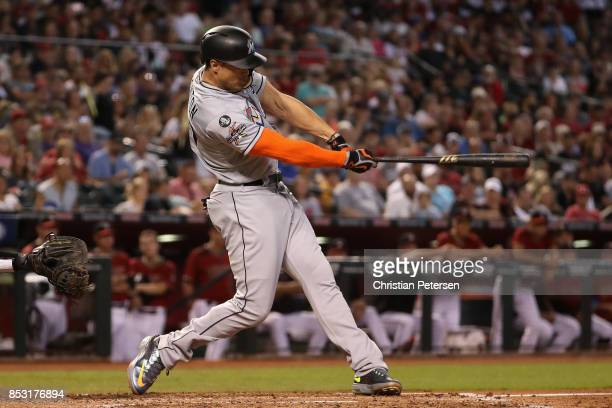 Giancarlo Stanton of the Miami Marlins hits a single against the Arizona Diamondbacks during the third inning of the MLB game at Chase Field on...