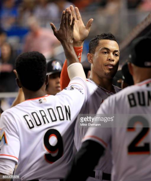 Giancarlo Stanton of the Miami Marlins is congratulated after scoring in the second inning during a game against the Atlanta Braves at Marlins Park...