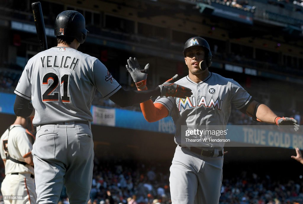 Giancarlo Stanton #27 of the Miami Marlins is congratulated by Christian Yelich #21 after Stanton hit a solo home run against the San Francisco Giants in the top of the 11th inning at AT&T Park on July 9, 2017 in San Francisco, California. The Marlins won the game 10-8.