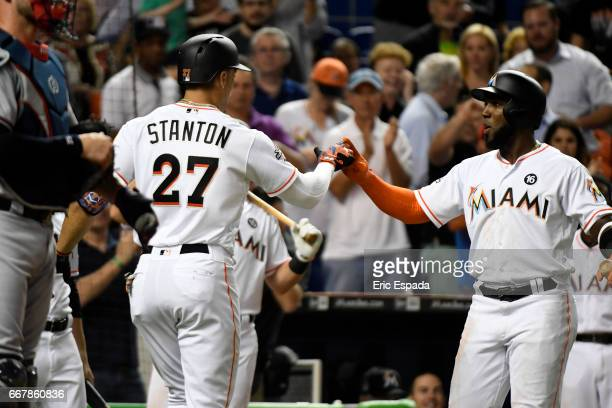 Giancarlo Stanton of the Miami Marlins is congratulated by Marcell Ozuna after hitting a home run in the 5th inning against the Atlanta Braves at...