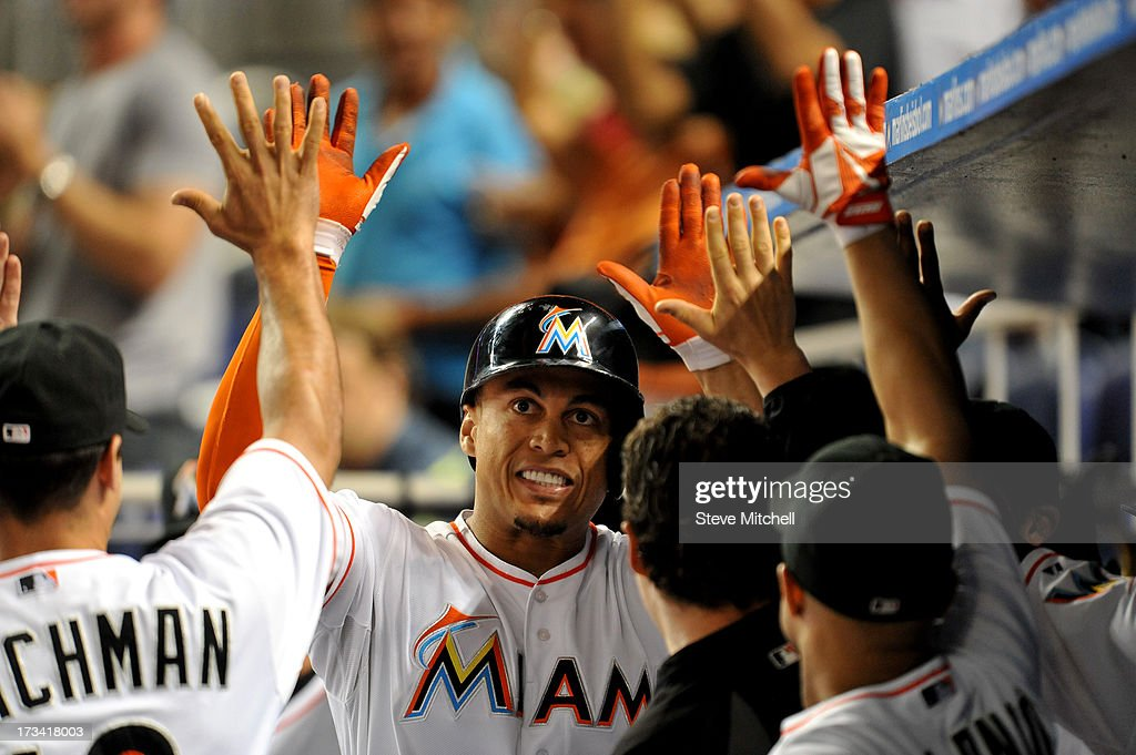 Giancarlo Stanton #27 of the Miami Marlins is greeted by teammates in the dugout after hitting a solo home run during the ninth inning against the Washington Nationals at Marlins Park on July 13, 2013 in Miami, Florida.