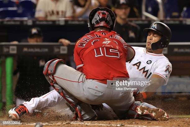 Giancarlo Stanton of the Miami Marlins is tagged out at home by Martin Maldonado of the Los Angeles Angels in the eighth inning during a game at...