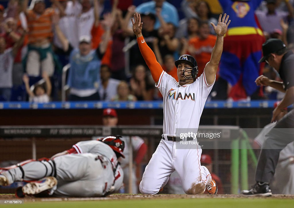 Giancarlo Stanton #27 of the Miami Marlins reacts after scoring beneath the tag from Carlos Ruiz #51 of the Philadelphia Phillies to score the winning run off a double by Marcell Ozuna of the Miami Marlins for a walk-off victory in the game at Marlins Park on May 1, 2015 in Miami, Florida.