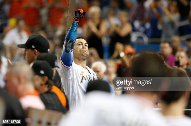 Giancarlo Stanton of the Miami Marlins reacts to fans on the dugout steps after striking out in the ninth inning during play against the Atlanta...