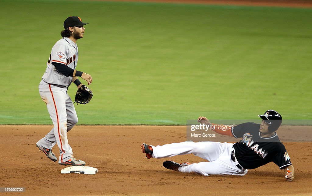 Giancarlo Stanton #27 of the Miami Marlins runs into a double play against Shortstop Brandon Crawford #35 of the San Francisco Giants at Marlins Park on August 16, 2013 in Miami, Florida.