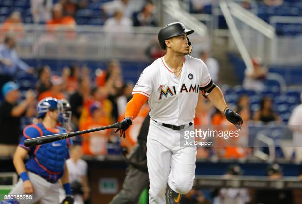 Giancarlo Stanton of the Miami Marlins watches his 56th home run of the season in front of Kevin Plawecki of the New York Mets in the eighth inning...