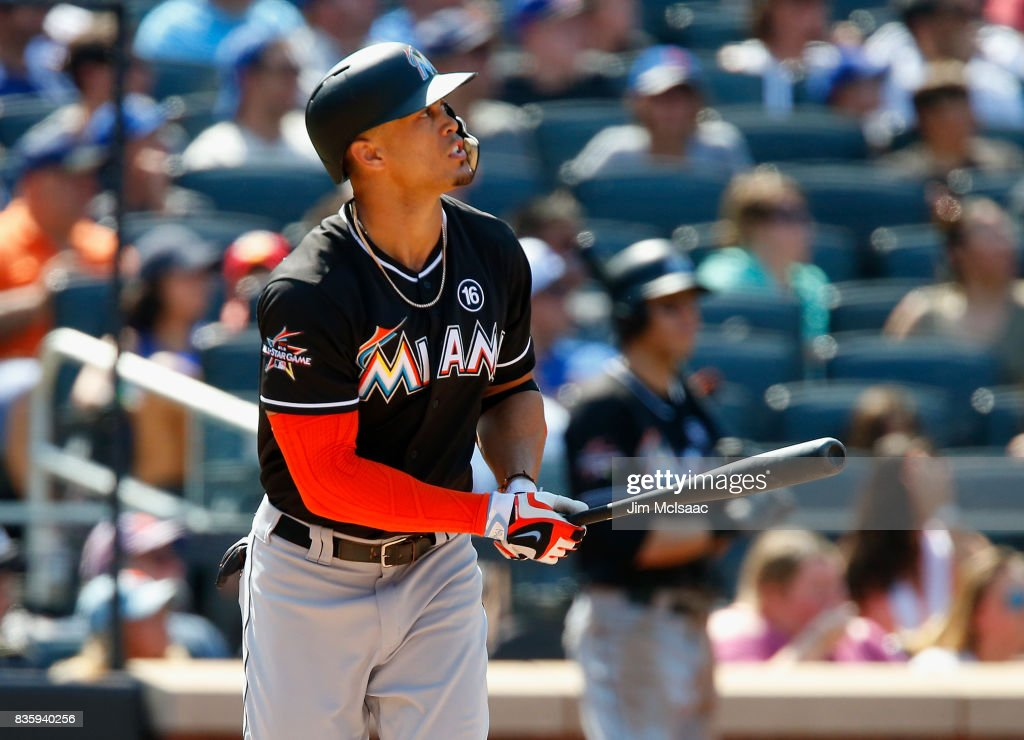 Giancarlo Stanton #27 of the Miami Marlins watches the flight of his seventh inning three run home run against the New York Mets at Citi Field on August 20, 2017 in the Flushing neighborhood of the Queens borough of New York City.