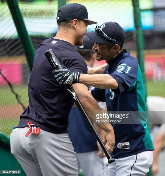 Giancarlo Stanton of the New York Yankees and Ichiro Suzuki of the Seattle Mariners hug before a game at Safeco Field on September 8 2018 in Seattle...